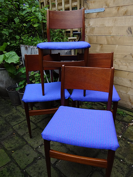 stack of vintage teak chairs recovered in vintage blue upholstery fabric
