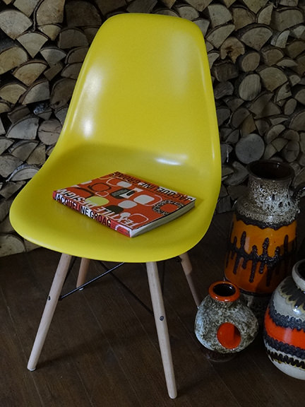 reproduction yellow DSW chair from Metro Furniture with collection of fat lava pottery vases