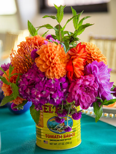 colourful tomato sauce tin upcycled as a vase for cut flowers