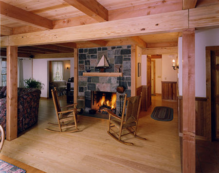 Pair of wooden rocking chairs in front of a traditional open fireplace