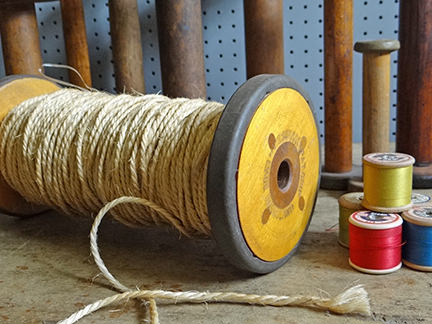 collection of vintage bobbins with string and threads