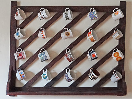 collection of vintage ceramic cups on an antique wooden rack