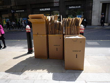 Parcelled up carboard boxes on a pavement