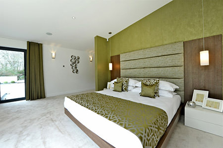 Bedroom with army green wall, bedding and headboard