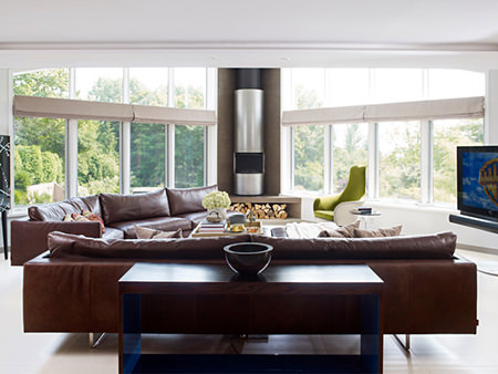 Light-filled sitting room with pair of large brown leather sofas