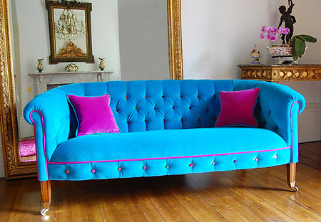 Turquoise upholstered sofa with bubblegum pink trim and cushions