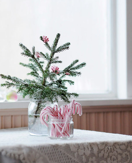 Sprig of decorated fir tree and glass jar of striped candy canes