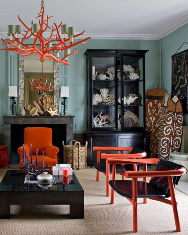 Eclectic lounge with coral coloured armchairs and chandelier