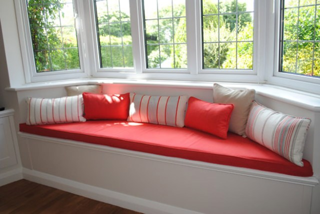 Window seat with coral coloured upholstery and cushions