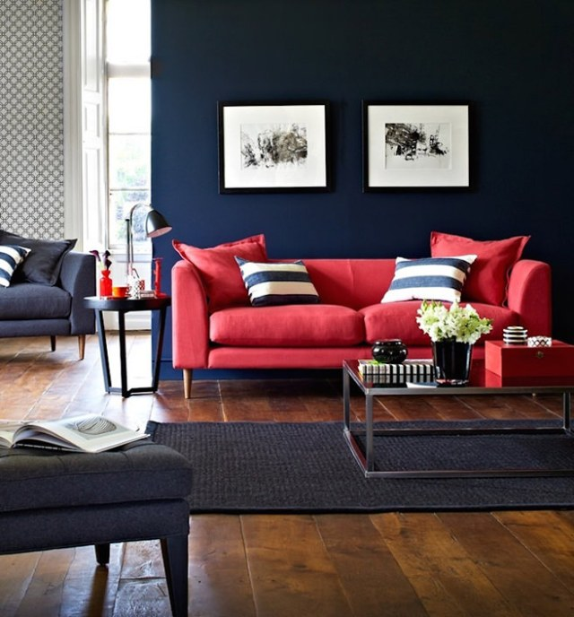 Coral colourd sofa in front of a midnight blue wall