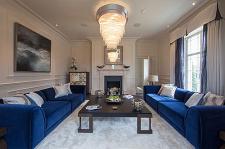 Pair of large corflower blue upholstered sofas in a sitting room