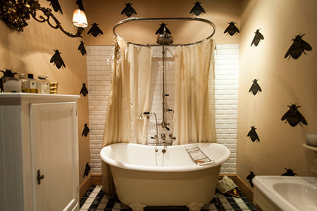 Bathroom with roll-top bath and bee print wallpaper
