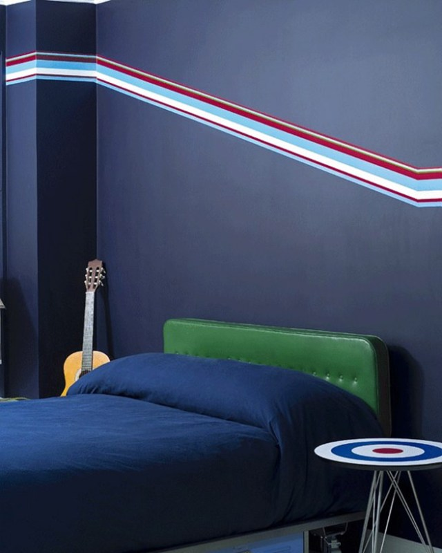 Boy's bedroom decorated in shades of blue with racing green bed head