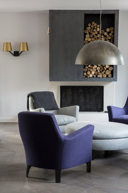 sitting room with purple armchairs and large steel ceiling pendant light