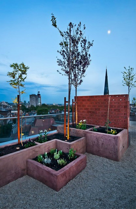 Urban roof terrace with red brick feature wall and terracotta planters