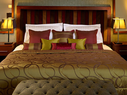 Mitre Linen bedding in shades of gold and claret