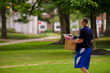 young man moving a cardboard box full of stuff