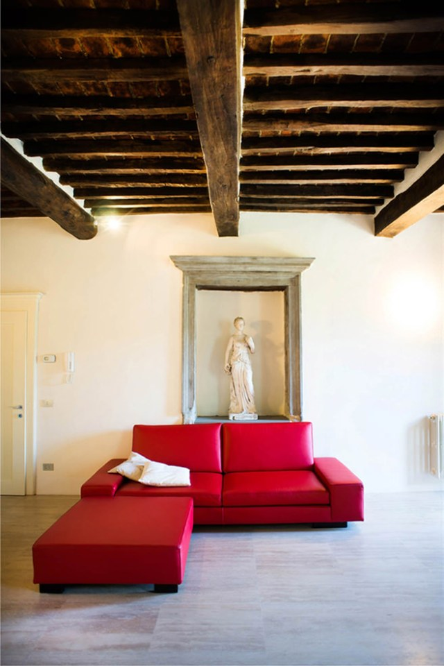 Tuscan villa interior with red L-shaped sofa and stone sculpture
