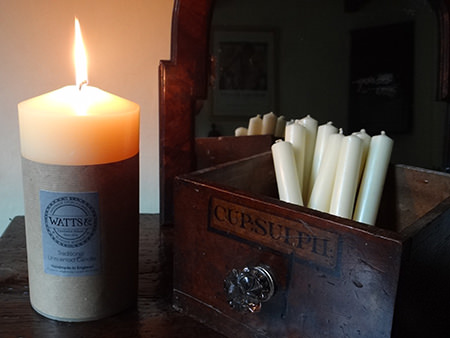 Lit Watts & Co pillar candle with church candles in an antique mahogany apothecary drawer