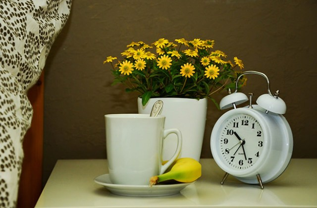 Bedside table with alarm clock, pot of flowers, cup & saucer, teaspoon and banana