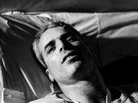 John McCain liggend op een bed in Hanoi Hilton