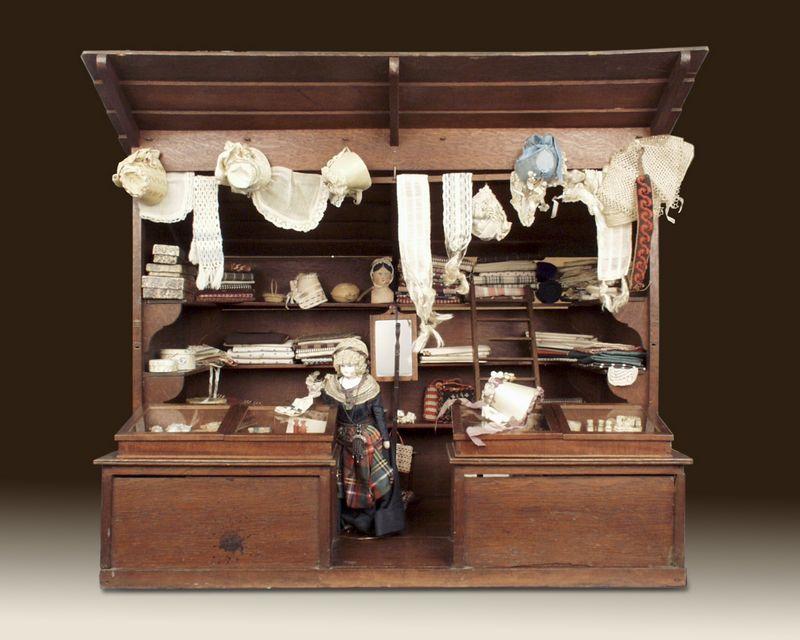 Manufactuurwinkel, gemaakt tussen 1875 en 1900 – foto door J & M Zweerts, Den Haag (Collectie Haags Historisch Museum) Deze manufactuurwinkel bestaat uit een open eikenhouten kast met een luifel. Hierin paste vrijwel alle koopwaar: diverse stoffen, doosjes, mandjes en standaarden voor hoedjes. In de kast hangt ook een spiegel met een ellestok, waarmee de stof werd opgemeten. Op de toonbank staan twee vitrinekastjes met glazen deksels. Hierin liggen toneelkijkers, naai-etuis, scharen, handspiegels en parfumflesjes. Ook aan de kleinste details werd gedacht: het winkelmeisje draagt een zilveren schaartje aan haar ketting. Hiermee kon ze de benodigde stof afknippen.