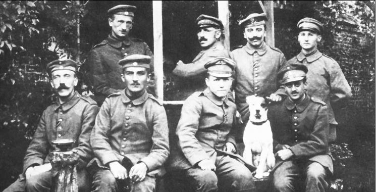 Hitler met zijn kameraden en zijn trouwe hondje Foxl in het gebied achter het front. Voorste rij van links naar rechts: Adolf Hitler, Balthasar Brandmayer, Anton Bachmann en Max Mund. Achterste rij van links naar rechts: Ernst Schmidt, Johann Sperl, Jakob Weiss en Karl Tiefenböck.