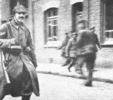 Bataljonskoerier Adolf Hitler in mei 1915 met zijn geweer over zijn schouder gehangen. Hitler is onderweg om een boodschap af te leveren. Deze foto verschijnt voor het eerst in de regimentsgeschiedenis van het 16e RIR.