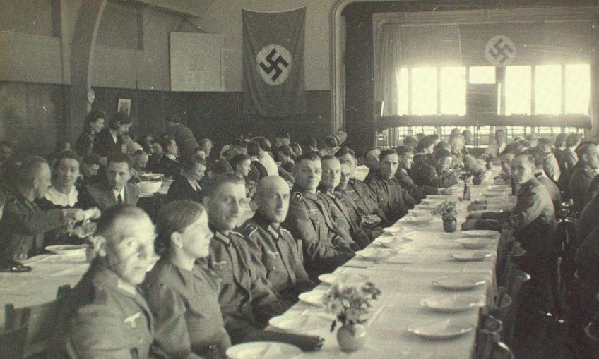 Gebruikers van een eenpansmaaltijd te Zaandam. Datum onbekend (eind 1942 - begin 1943). Fotograaf onbekend. Collectie Gemeentearchief Zaanstad.