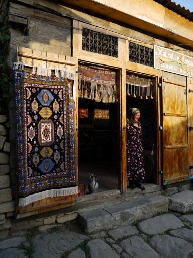 Old carpet seller in doorway with hanging carpets - Lahıc, Azerbaijan