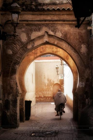 KOEphotography - Morocco, man on the bicycle pedalling under an arch