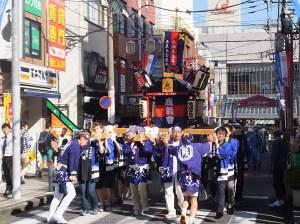 慶應学生と地元有志による神輿(みこし)が「ケイ、オー!」の掛け声とともに、駅前中央通りとメイルロードを巡回しました