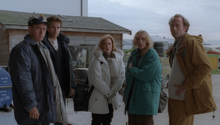 Mulder and Scully stand on an airfield base with the guest characters in the X-Files epsidode Ice.