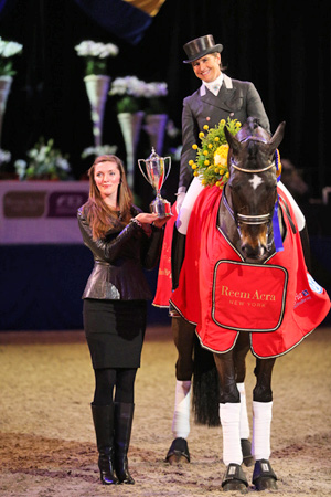 Tinne Vilhelmson-Silfven and Don Auriello being presented with the Reem Acra Cup by Reem Acra representative Heather Schmidt after the Swedish horse-and-rider partnership topped the fourth leg of the Reem Acra FEI World Cup™ Dressage 2012/2013 series at Stockholm, Sweden yesterday.  Photo: FEI/Peter Zachrisson.
