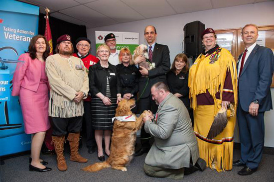 Veterans, representatives from St John Ambulance, MP Royal Galipeau and therapy dogs Lucy and Tulip show their enthusiasm for the funding announcement for studying how dogs and horses can improve the overall mental health and well-being of Vétérans (CNW Group/Veterans Affairs Canada).
