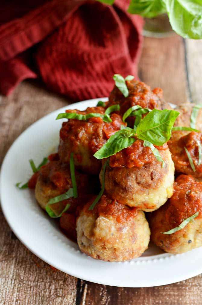 Mozzarella-Stuffed Chicken Parm Meatballs!  All the flavors of chicken parmesan in a fun-to-eat bite!  Click through to see a picture of the mozzarella-y inside and get the recipe!  | hostthetoast.com