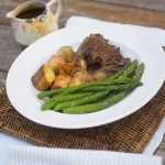 Slow-cooked bolar blade roast served with roast potatoes and steamed asparagus