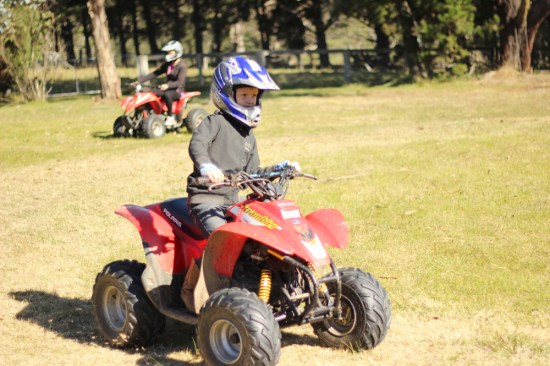 Alfie on the quad bike with the 'senior' in the background.