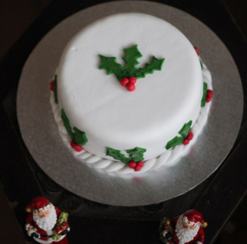 A Christmas Cake surrounded with holly
