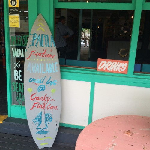 The entrance is beside the surfboard