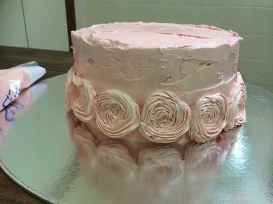 Start by piping roses around the bottom of the cake