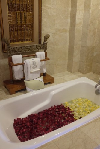 A very welcoming bath tub with rose and frangipani petals.