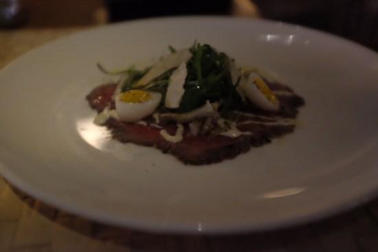 Black Angus Beef Carpaccio with quail eggs, roast garlic aioli, rocket, artichoke: About $11.40