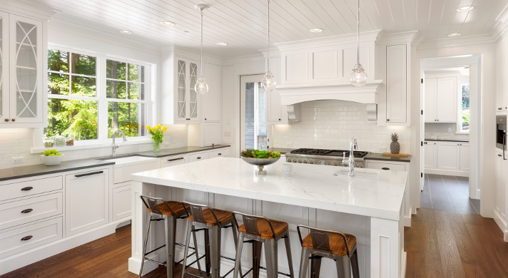 White Kitchen Interior with Island, Sink, Cabinets, and Hardwood Floors in New Luxury Home
