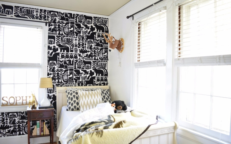 A Gender neautral kids' bedroom with a DIY graphic black and white animal fabric wall.