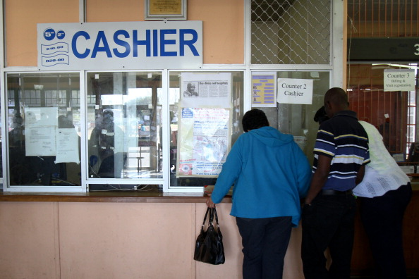 "Patients pay a cashier for treatment at Natalspruit hospital in Katlehong, South Africa, on Monday, Sept. 19, 2011. ""There is a base of 28.5 million people in the African market where there will be demand for the healthcare,"" Andre Meyer, Medscheme Ltd.'s chief executive officer said. Photographer: Nadine Hutton/Bloomberg via Getty Images"