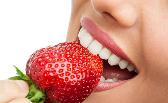 Macro close up of woman's mouth eating strawberry.