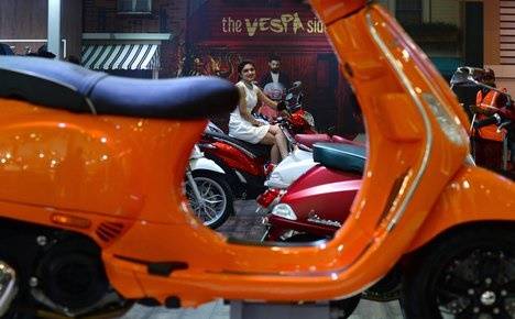 A model sits on a Vespa Liberty S scooter at the Indian Auto Expo 2016 in Greater Noida some 45kms east of New Delhi on February 4, 2016. India's flagship auto show opened its doors in New Delhi with a new batch of diesel-guzzling SUVs on proud display, despite industry uncertainty about a pollution crackdown targeting motorists in the capital. More than 80 vehicle launches were expected at the Auto Expo 2016, the biggest edition in the show's 30-year history, with the Fiat Chrysler-owned Jeep making its India debut and hoping to capitalise on the popularity of sports utility vehicles. AFP PHOTO / SAJJAD HUSSAIN / AFP PHOTO / SAJJAD HUSSAIN