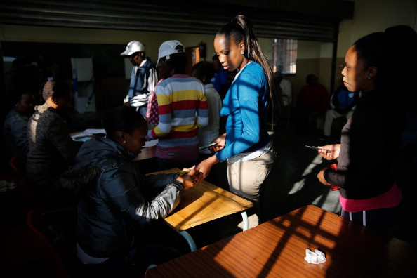 JOHANNESBURG, SOUTH AFRICA - MAY 07:  Several young women voters stand in line to have their hands marked and their identification checked before voting at the Orlando West Voting Station at the Orlando West Secondary School during the 2014 South African General Election on May 7, 2014 in the Soweto Township in Johannesburg, South Africa. Polls have opened in South Africa's fifth general election since the end of apartheid over 20 years ago. President Jacob Zuma is expected to return to power with the ANC party however his election campaign has been marred by allegations of corruption and he is expected to lose some ground to other parties.  (Photo by Jemal Countess/Getty Images)