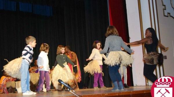 Joven de Uganda enseña danzas a un grupo de niños de Riotinto.